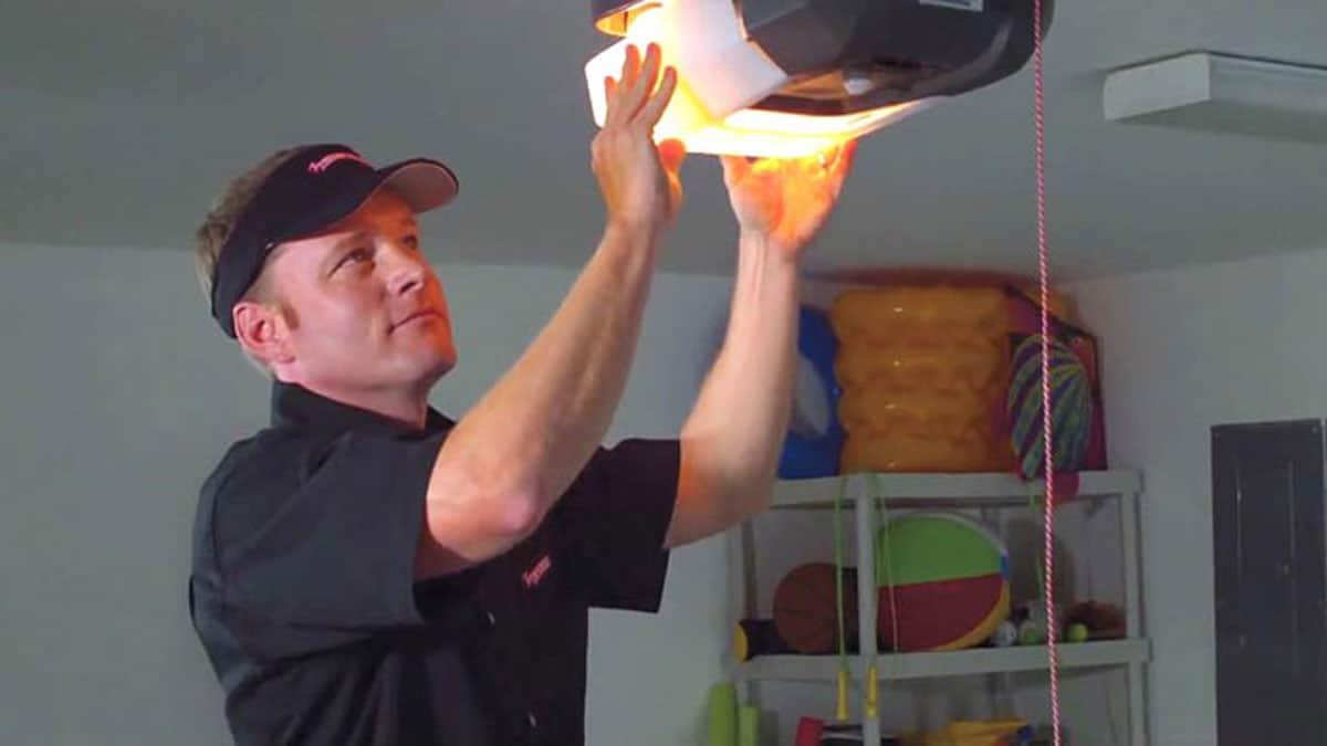 man inspecting garage door opener
