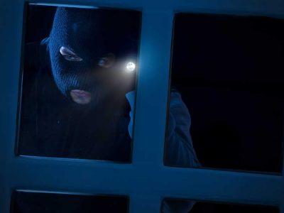 burglar looking in window of house