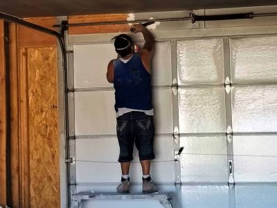 construction worker installing a rollup garage door with spring